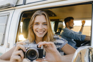 Portrait of happy woman with camera leaning out of window of a camper van with man driving - GUSF01424