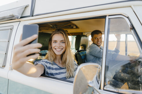 Portrait of happy woman taking a selfie in a camper van with man driving - GUSF01427