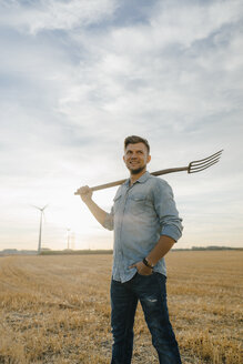 Portrait of smiling young man holding pitchfork standing on stubble field - GUSF01430
