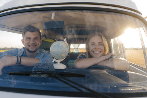 Portrait of happy young couple on a trip in camper van - GUSF01433