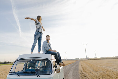 Happy couple on roof of a camper van in rural landscape - GUSF01436