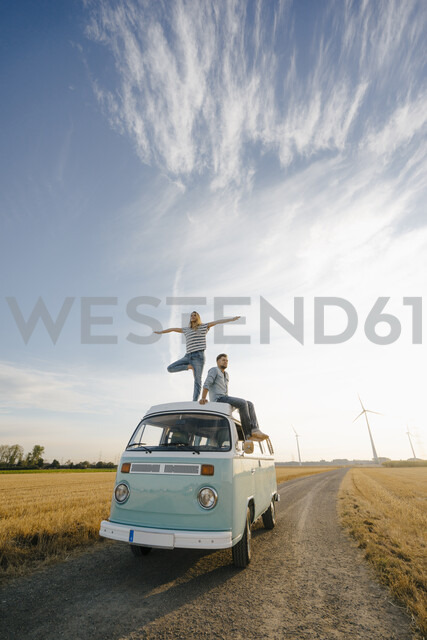 Young couple on roof of a camper van in rural landscape - GUSF01439
