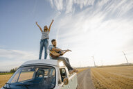 Happy couple with guitar on roof of a camper van in rural landscape - GUSF01442