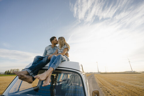 Couple kissing on roof of a camper van in rural landscape - GUSF01445