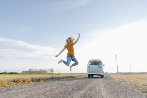 Exuberant young woman jumping on dirt track at camper van in rural landscape - GUSF01451