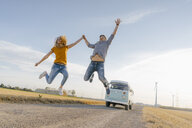Exuberant couple jumping on dirt track at camper van in rural landscape - GUSF01454