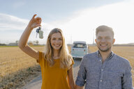 Portrait of happy young couple with car key on dirt track at camper van in rural landscape - GUSF01457