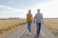 Young couple walking on dirt track at camper van in rural landscape - GUSF01460