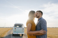 Young couple kissing at camper van in rural landscape - GUSF01463