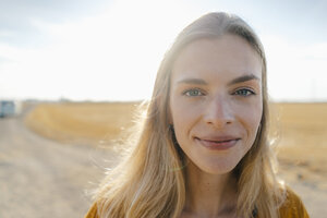 Portrait of smiling young woman in rural landscape - GUSF01475