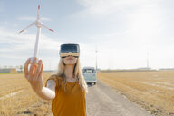 Young woman with VR glasses at camper van in rural landscape holding wind turbine model - GUSF01478