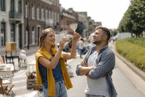 Belgium, Tongeren, happy young couple with glasses on an antique flea market - GUSF01484