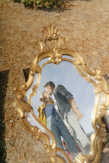 Affectionate young couple kissing reflected in vintage mirror - GUSF01490
