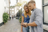 Netherlands, Maastricht, young couple looking at cell phone the city - GUSF01496