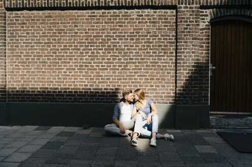 Netherlands, Maastricht, young couple having a break in the city sitting on sidewalk - GUSF01502
