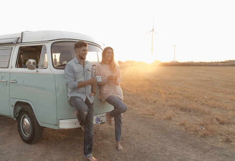 Happy young couple standing at camper van in rural landscape at sunset - GUSF01538