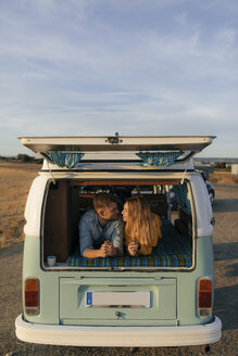 Young couple lying in camper van in rural landscape - GUSF01544