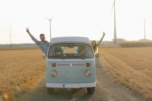 Happy couple leaning out of window of a camper van in rural landscape - GUSF01547