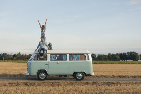 Happy couple on roof of a camper van in rural landscape - GUSF01550