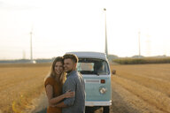 Happy affectionate young couple at camper van in rural landscape - GUSF01559