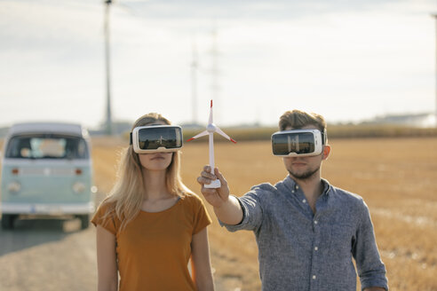 Young couple with VR glasses at camper van in rural landscape holding wind turbine model - GUSF01568