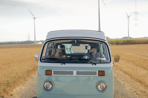 Smiling couple wearing VR glasses driving camper van in rural landscape - GUSF01571