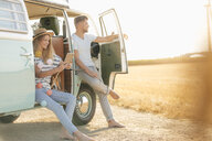 Young couple relaxing at camper van in rural landscape - GUSF01574