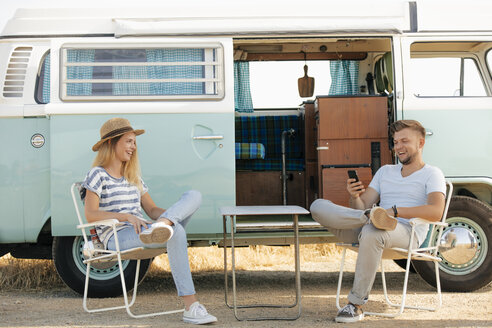 Happy young couple sitting on camping chairs at camper van with cell phone - GUSF01577