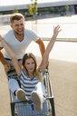Carefree young man pushing girlfriend in a shopping cart - GUSF01580