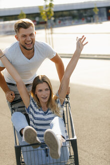 Carefree young man pushing girlfriend in a shopping cart - GUSF01580
