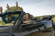 Happy couple driving with raise darms in convertible car on a country road - GUSF01589