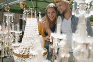Belgium, Tongeren, happy young couple on an antique flea market - GUSF01616