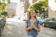 Netherlands, Maastricht, smiling blond young woman holding ice cream cone in the city - GUSF01619