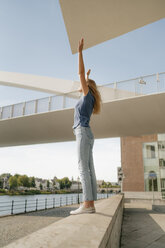 Netherlands, Maastricht, young woman standing on a wall at the riverside with raised arms - GUSF01622