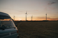 Camper van in rural landscape with wind turbines at sunset - GUSF01625