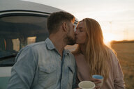 Young couple kissing at camper van in rural landscape - GUSF01628