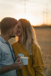Happy young couple holding mugs kissing in rural landscape - GUSF01631