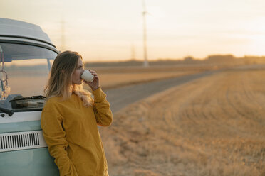 Young woman drinking from mug at camper van in rural landscape at sunset - GUSF01634