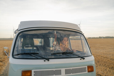 Smiling young woman driving camper van in rural landscape - GUSF01640