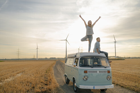 Young couple on roof of a camper van in rural landscape - GUSF01643