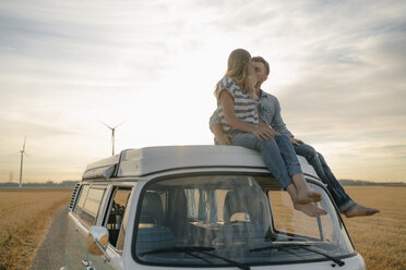 Couple kissing on roof of a camper van in rural landscape - GUSF01646