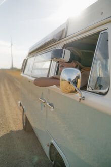 Happy woman wearing VR glasses leaning out of window of a camper van - GUSF01652