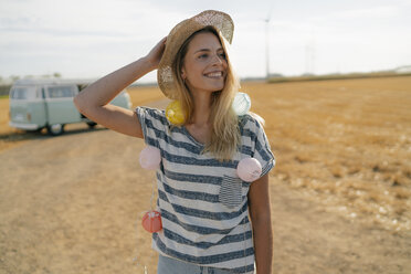 Happy young woman at camper van in rural landscape - GUSF01655