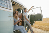 Young couple with cell phones relaxing at camper van in rural landscape - GUSF01658