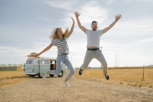 Exuberant couple jumping on dirt track at camper van in rural landscape - GUSF01661