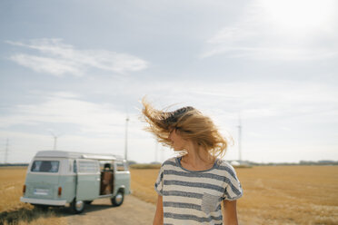 Blong young woman at camper van in rural landscape shaking her hair - GUSF01664