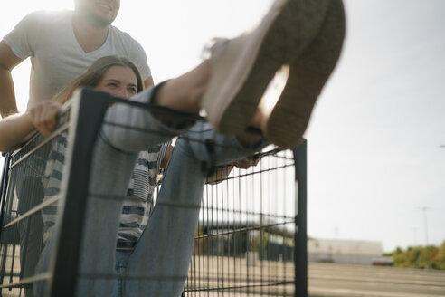 Carefree young man pushing girlfriend in a shopping cart - GUSF01667