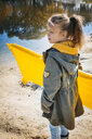 Girl with yellow airbed on the beach in autumn - HMEF00079