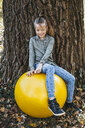 Portrait of smiling girl sitting on yellow gym ball leaning against tree trunk - HMEF00091
