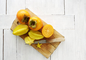 Whole and slices Kakis and star fruits on wooden board - KSWF01999